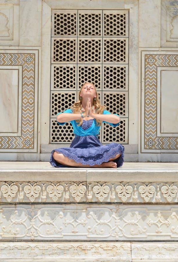 Ung kvinna som mediterar på väggen av Taj Mahal arkivbild