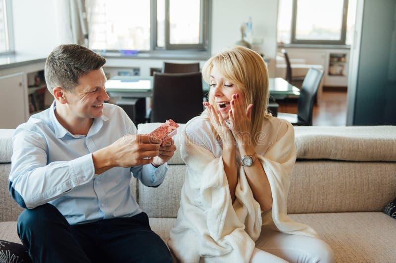 Ung kvinna som mottar en röd ask för överraskninggåva från hennes pojkvän på soffan arkivbild