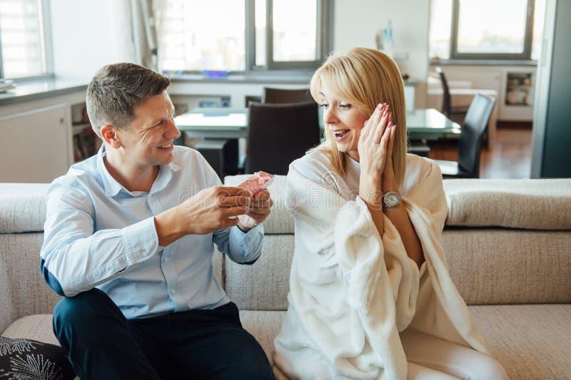 Ung kvinna som mottar en röd ask för överraskninggåva från hennes pojkvän på soffan royaltyfri foto