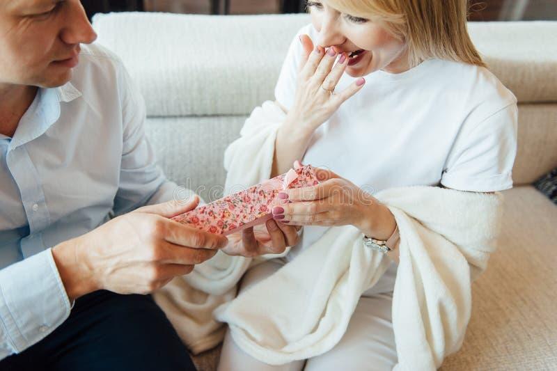 Ung kvinna som mottar en röd ask för överraskninggåva från hennes pojkvän på soffan arkivbilder