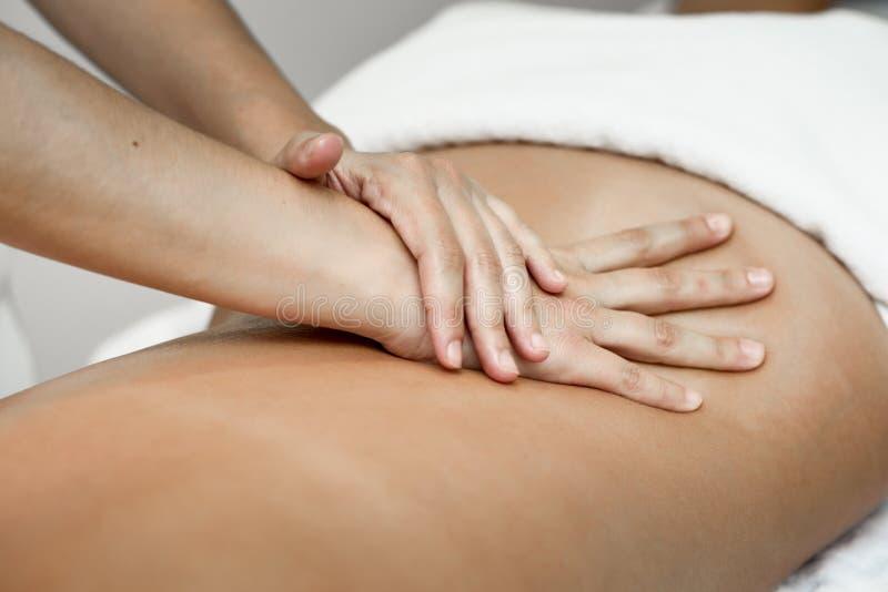 Ung kvinna som mottar en tillbaka massage i en brunnsortmitt royaltyfria bilder
