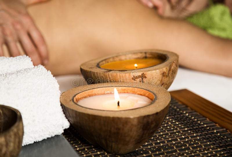 Ung kvinna som mottar en tillbaka massage i brunnsortsalongen närbild av en stearinljus och handdukar royaltyfria foton