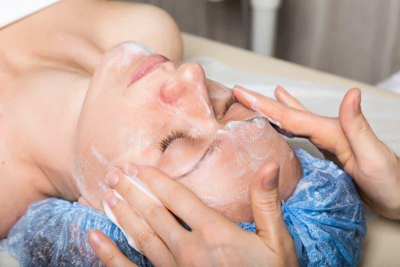 Ung kvinna som ner ligger i en brunnsortsalong och har en ansikts- skönhetbehandling De kosmetiska tillvägagångssätten för framsi royaltyfri bild