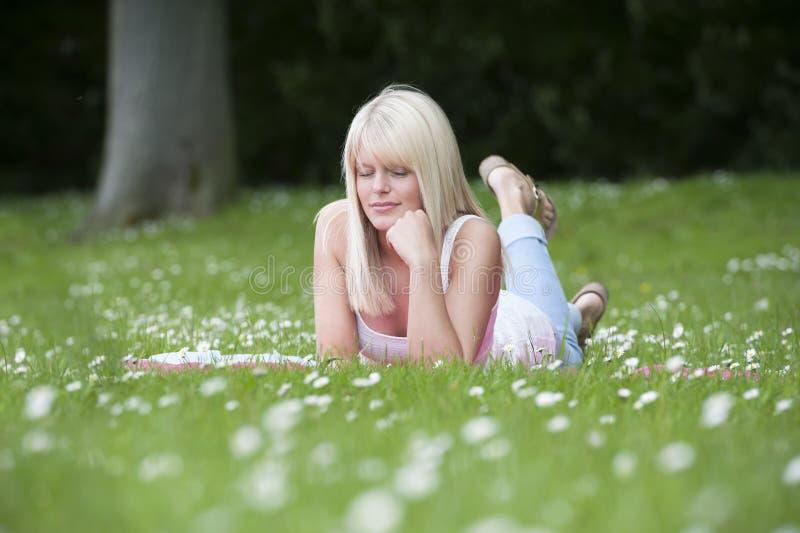 Ung kvinna som ner ligger i ett gräsfält med tusenskönor arkivbild