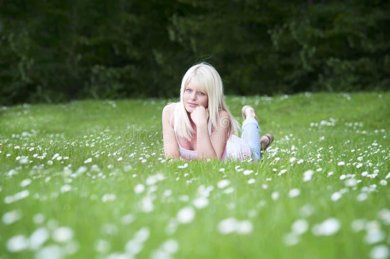 Ung kvinna som ner ligger i ett gräsfält med tusenskönor royaltyfri foto