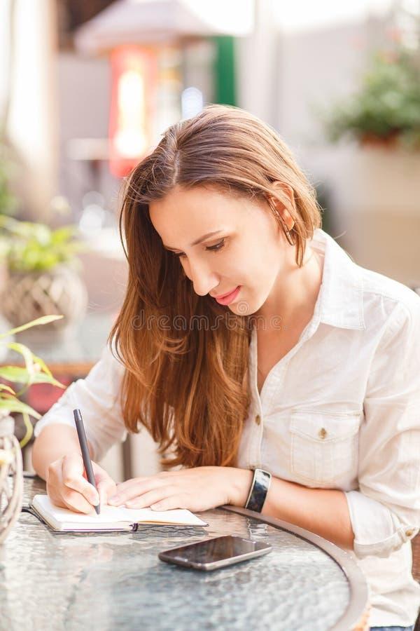Ung kvinna som ner skriver in i hennes anteckningsbok royaltyfri bild