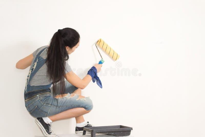 Ung kvinna som nyinreder hennes hus arkivfoto