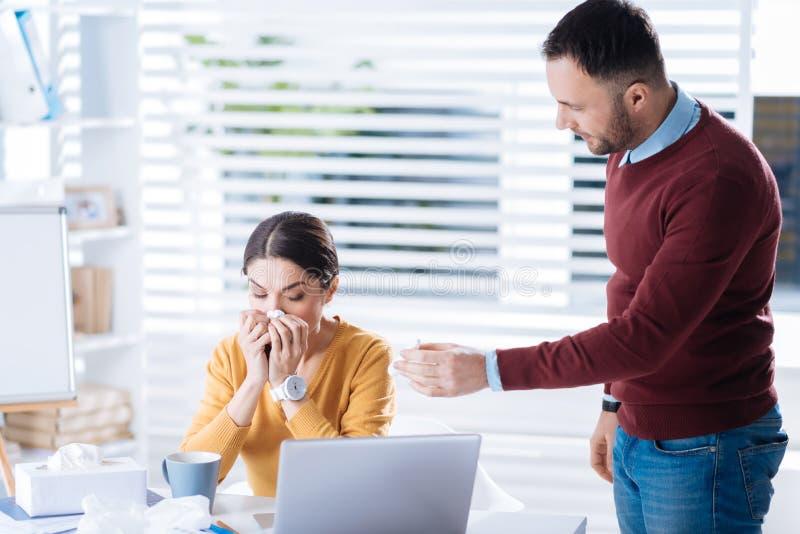 Ung kvinna som nyser medan hennes vänliga kollega som erbjuder hennes nasala droppar arkivbild