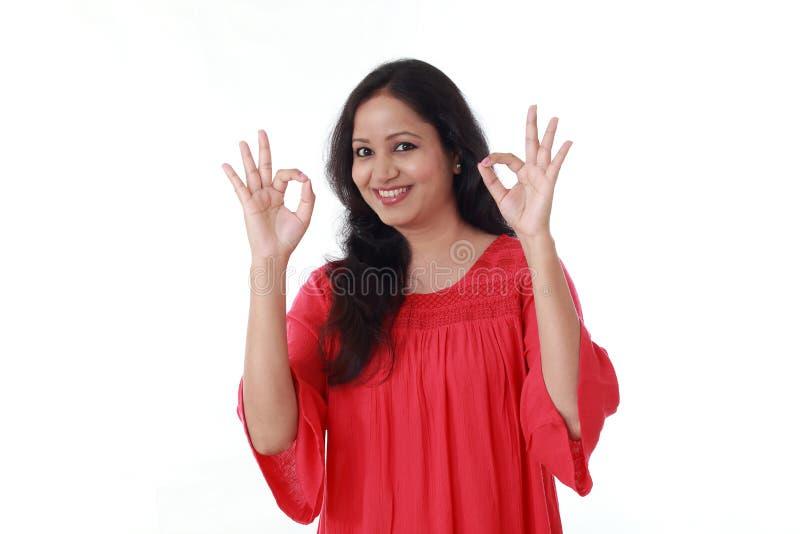 Ung kvinna som ok gör gest mot vit arkivfoton