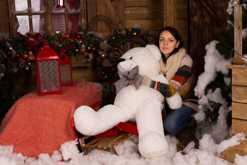 Ung kvinna som omfamnar den stora dockan för vit björn fotografering för bildbyråer