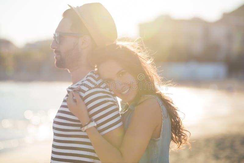 Ung kvinna som omfamnar hennes pojkvän på att le för sjösida arkivfoton