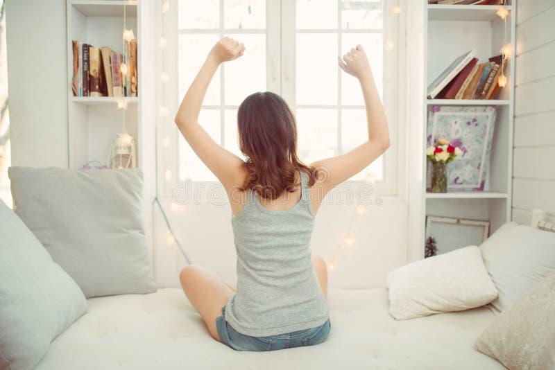 Ung kvinna som outstretching hennes armar som sitter p? s?ngen efter s?mn f?r bra natt arkivfoton