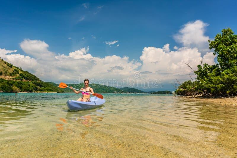 Ung kvinna som paddlar under semester i en idyllisk loppdestin fotografering för bildbyråer