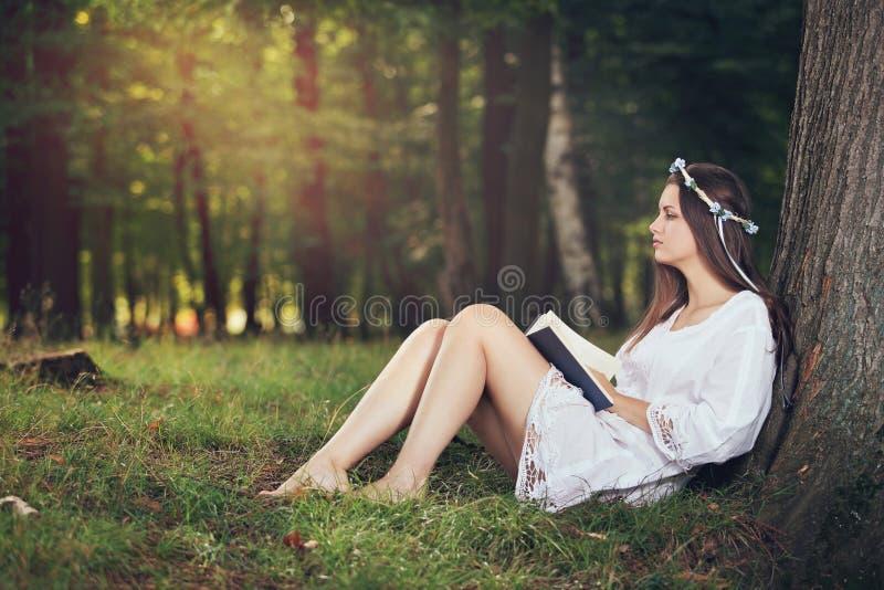 Ung kvinna som pecefully läser i härlig skog fotografering för bildbyråer