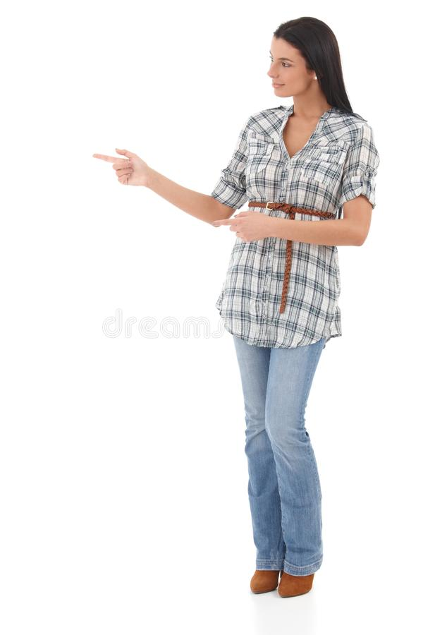 Ung kvinna som pekar och ser till höger sida arkivbild
