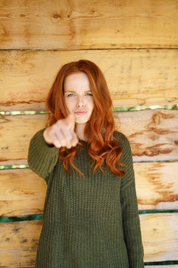 Ung kvinna som pekar på kameran royaltyfri fotografi