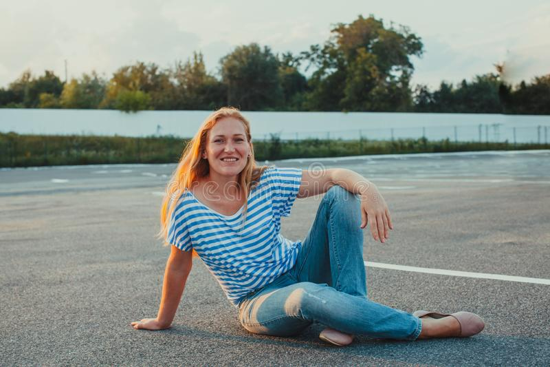 Ung kvinna som placerar på asfalt som ser kameran royaltyfri bild