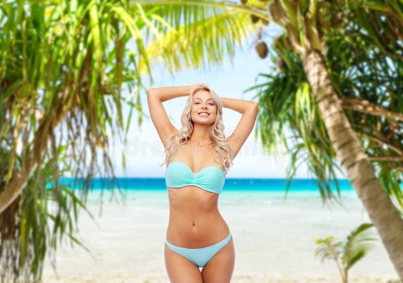 Ung kvinna som poserar i bikini på stranden fotografering för bildbyråer