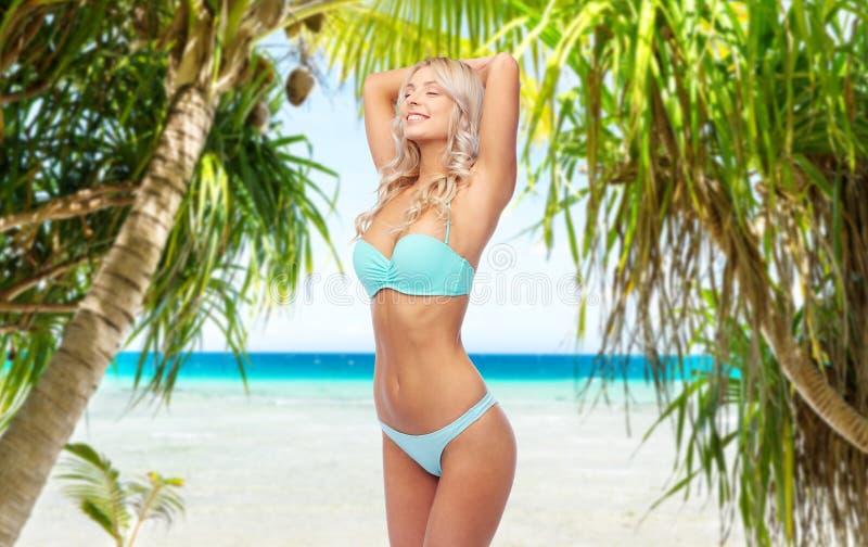 Ung kvinna som poserar i bikini på stranden royaltyfri bild