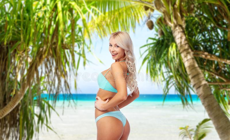 Ung kvinna som poserar i bikini på stranden arkivfoto