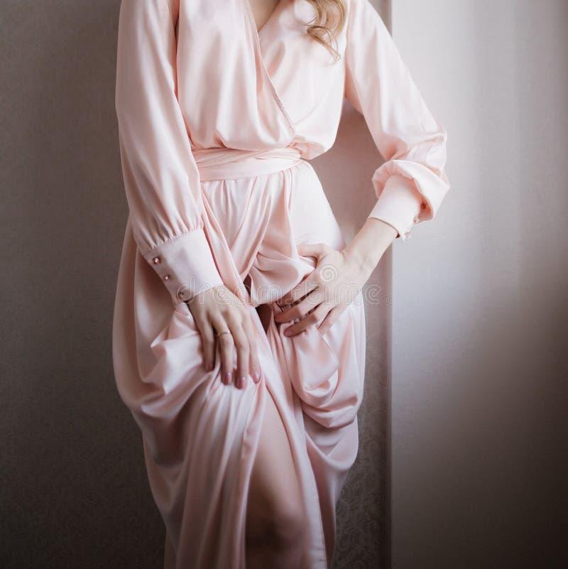 Ung kvinna som poserar i ett vitt br?llopskl?nningslut upp arkivfoto