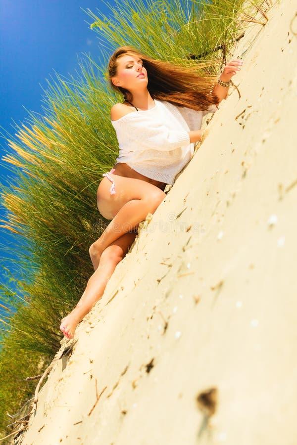 Ung kvinna som poserar i gräs- dyn arkivbilder