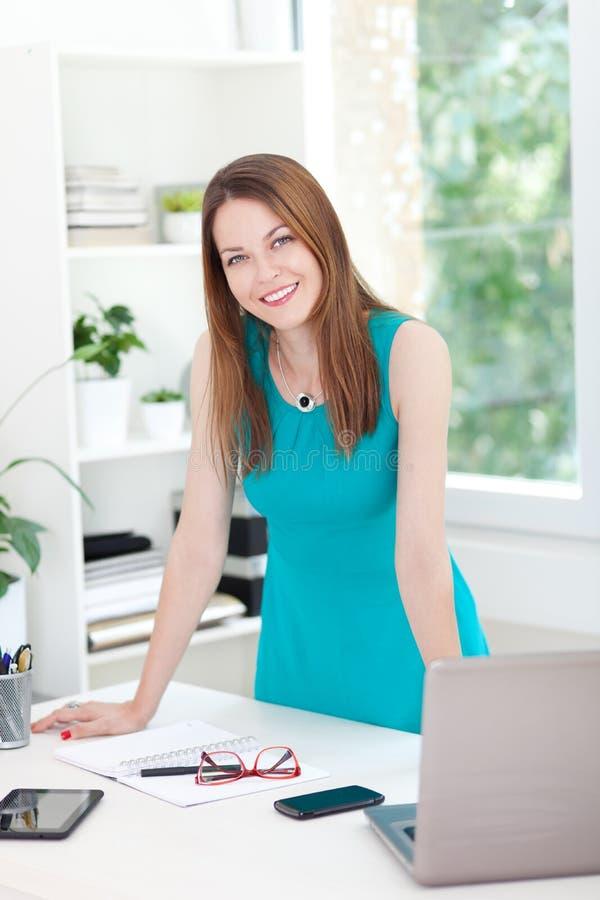 Ung kvinna som poserar i kontoret fotografering för bildbyråer