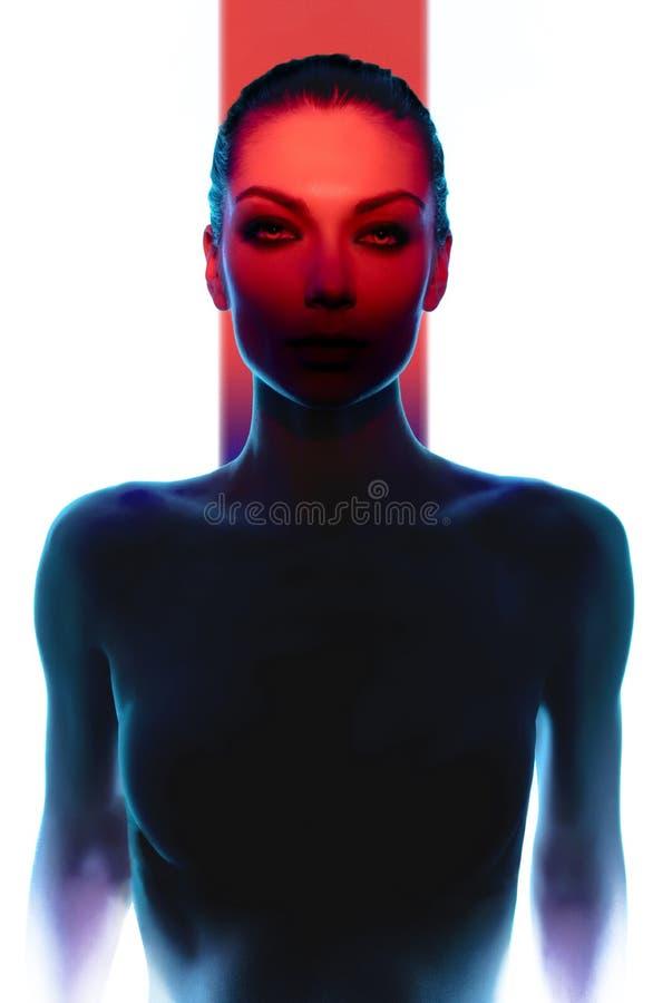 Ung kvinna som poserar i mörker med rött ljus arkivbild