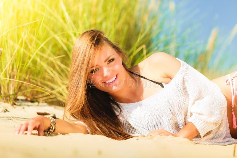 Ung kvinna som poserar på den gräs- dyn royaltyfri bild