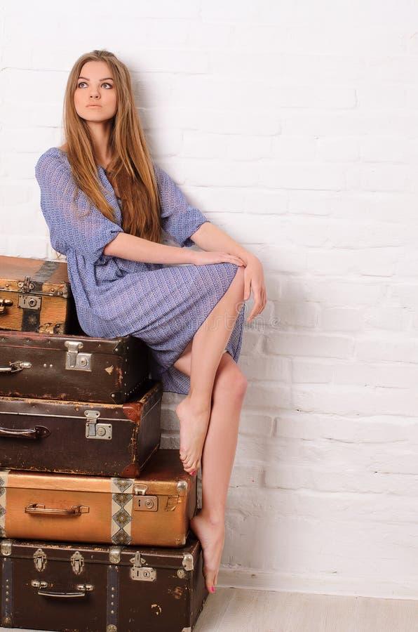 Ung kvinna som poserar på högen av resväskor fotografering för bildbyråer