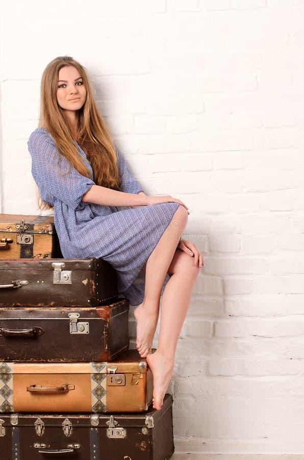 Ung kvinna som poserar på högen av resväskor arkivfoton