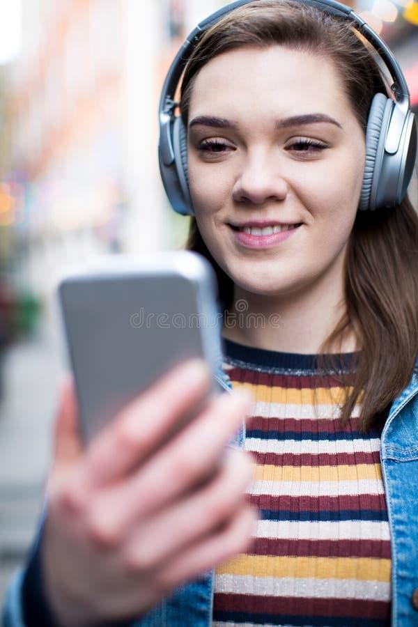 Ung kvinna som promenerar gatan som strömmar musik från mobila Pho royaltyfri foto