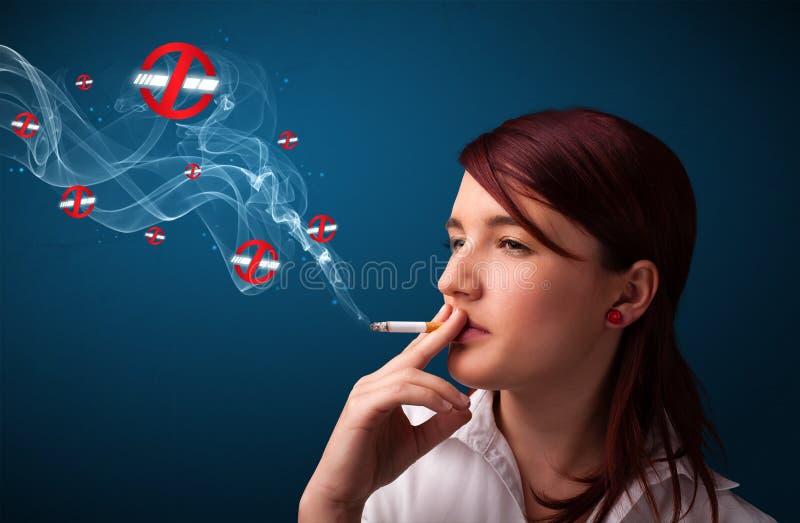 Ung kvinna som röker den farliga cigaretten med inget - röka undertecknar royaltyfri fotografi