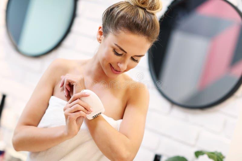 Ung kvinna som rakar armhålor i badrum arkivbilder