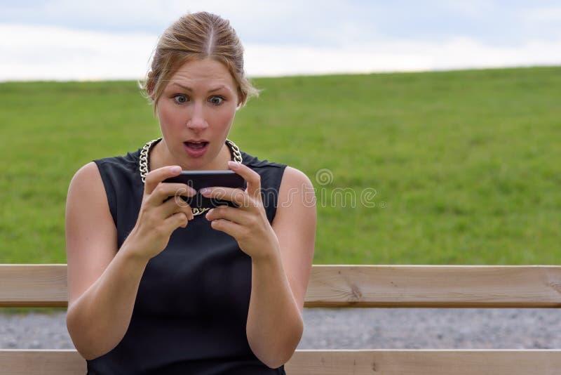 Ung kvinna som reagerar i chock till sms royaltyfria bilder