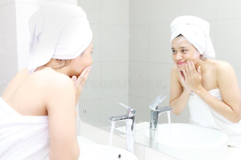 Ung kvinna som rentvår hennes framsida i badrummet royaltyfri foto