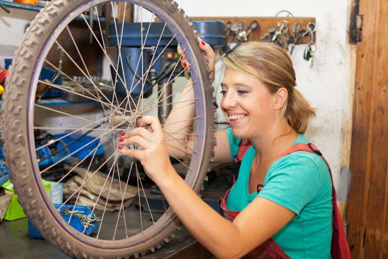 Ung kvinna som reparerar cykelhjulet arkivfoton