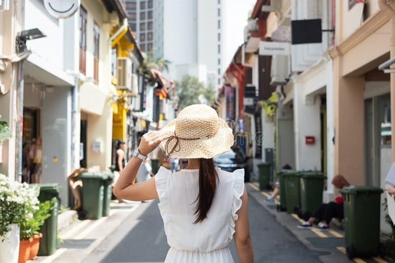 Ung kvinna som reser med den vit kl?nningen och hatt, lycklig asiatisk handelsresande som g?r p? Haji Lane, och arabisk gata i Si arkivbild