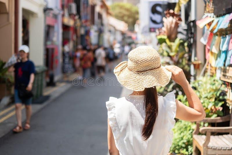 Ung kvinna som reser med den vit kl?nningen och hatt, lycklig asiatisk handelsresande som g?r p? Haji Lane, och arabisk gata i Si royaltyfri foto