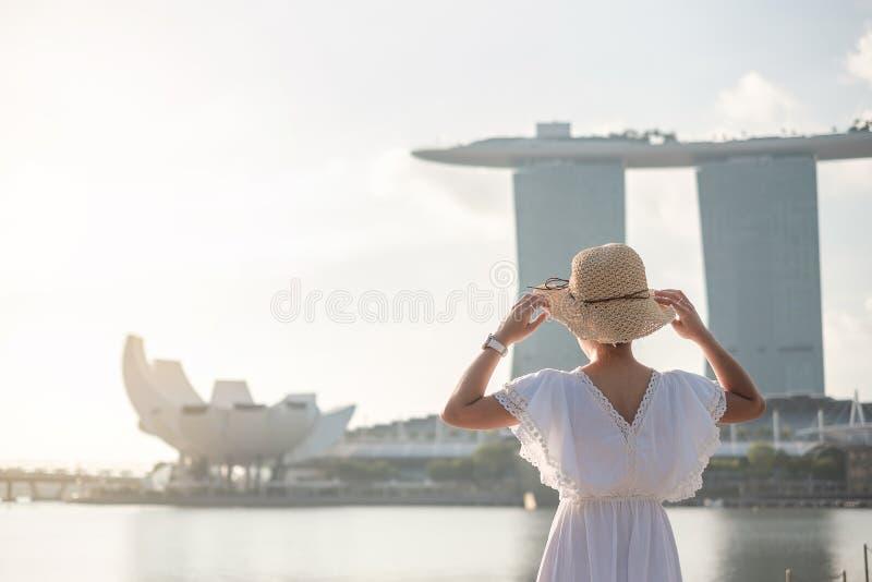 Ung kvinna som reser med hatten i morgonen, lyckligt asiatiskt handelsresandebesök i Singapore stadscentrum gr?nsm?rke och popul? royaltyfri fotografi