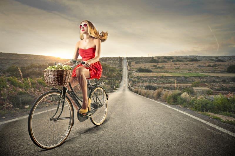 Ung kvinna som rider en cykel royaltyfri fotografi