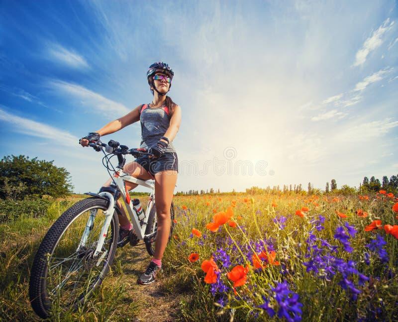 Ung kvinna som rider en cykel på en blommande vallmoäng