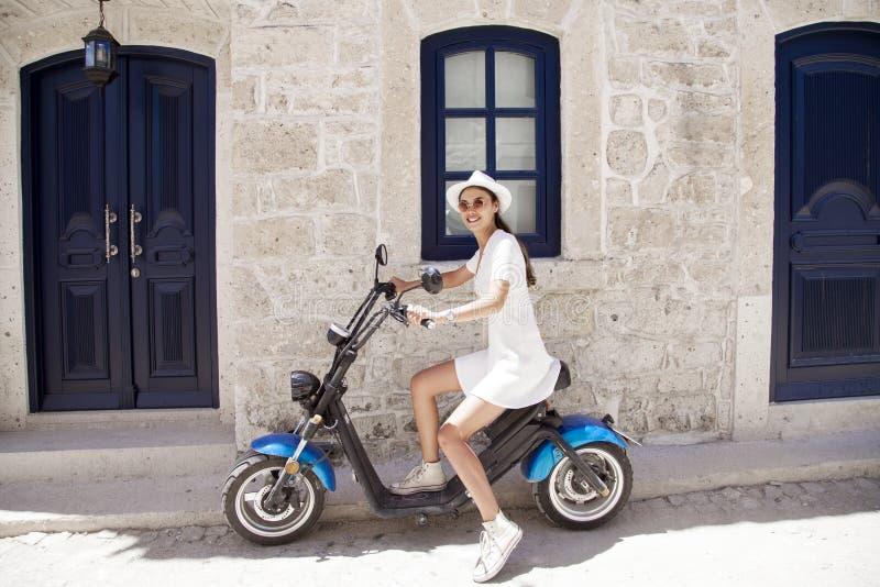 Ung kvinna som rider en moped Ung ryttare som tycker om på tur Aff?rsf?retag- och semesterbegrepp arkivbild