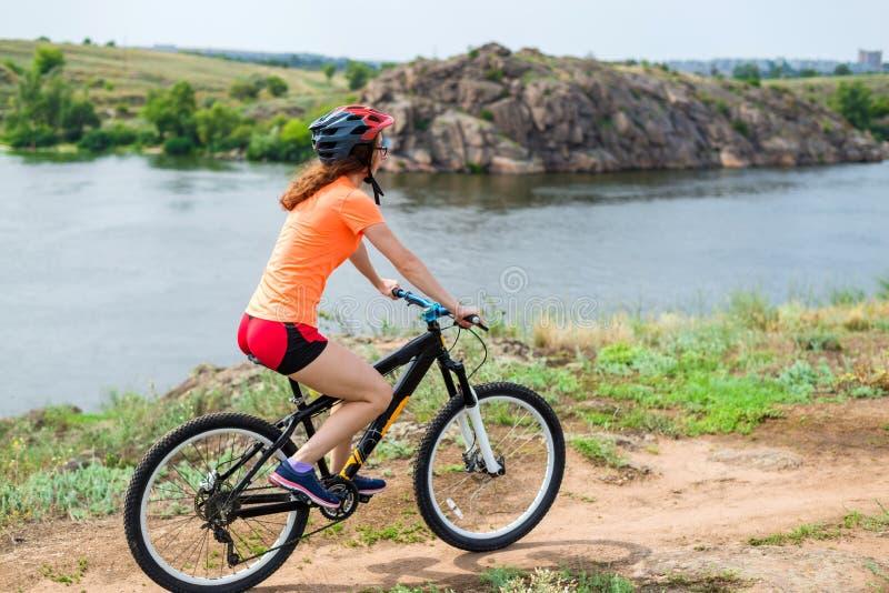 Ung kvinna som rider en mountainbike, en aktiv livsstil arkivbild