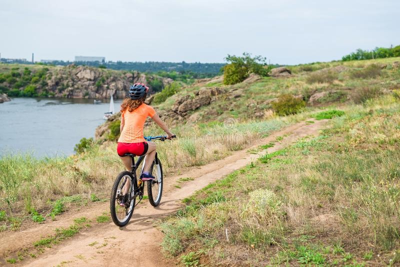 Ung kvinna som rider en mountainbike, en aktiv livsstil arkivfoto