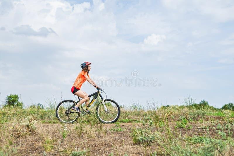 Ung kvinna som rider en mountainbike, en aktiv livsstil fotografering för bildbyråer