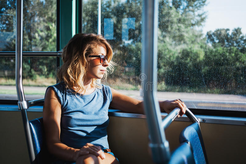 Ung kvinna som rider en offentlig buss arkivfoton