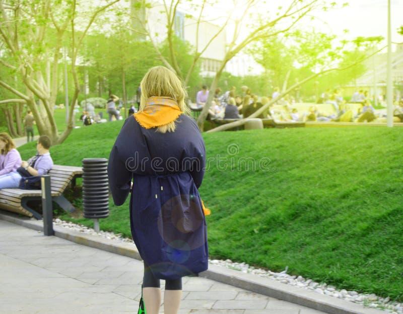 Ung kvinna som rider hennes sparkcykel i parkera, sikten fr?n baksidan arkivfoto