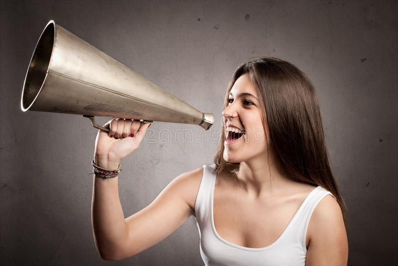 Ung kvinna som ropar med en gammal megafon royaltyfria bilder