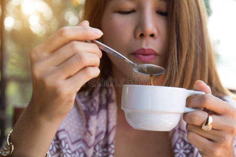 Ung kvinna som rymmer att dricka kaffe genom att använda skeden som blåser varmt kaffe, innan att dricka i morgonen hemma Asiatis arkivfoto